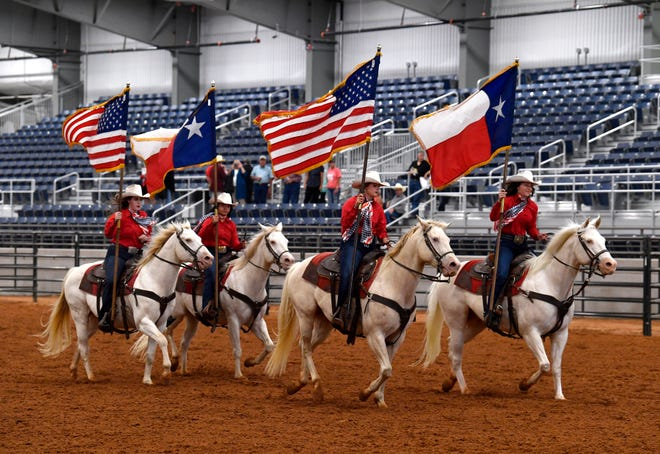 Members of the Six White Horses, the Hardin-Simmons University equestrian team, ride across the new Taylor Telecom Arena at the Taylor County Expo Center Thursday.