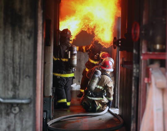 Flames erupt when a door is opened by WRG Fire Training Simulation Systems instructors as they conduct a maritime firefighter training for Navy sailors at the Bremerton International Emergency Services Training Center on Thursday.