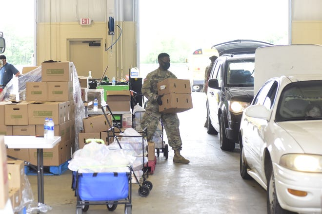 A National Guard member loads boxes of food into a vehicle Friday afternoon inside the Galion School District's bus garage. Nearly 500 Galion residents collected the free shelf-stable items during the food drive.