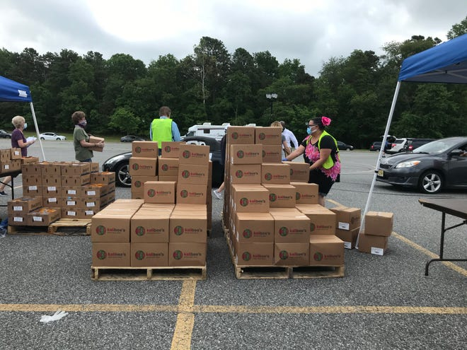 Volunteers grab boxes to put into cars at a food giveaway Friday at Camden County College.