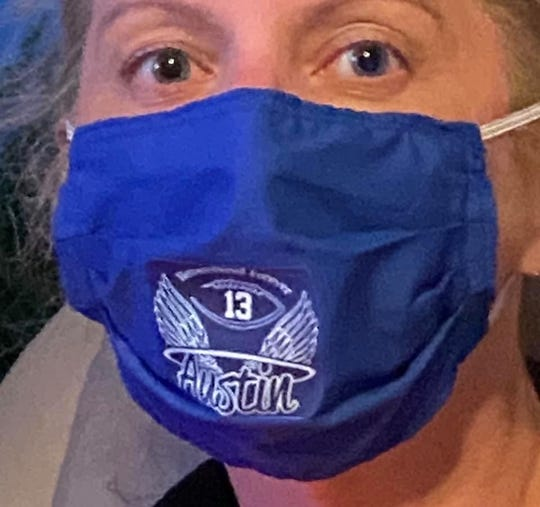 Kim Muckenfuss of Washington Township is shown wearing a facemask being made in her late son's honor. The masks are being sold for $10 and are going towards fundraising efforts for the Austin Muckenfuss Scholarship Fund, which has given out more than $33,000 in scholarships to graduating seniors since her son died in 2015.