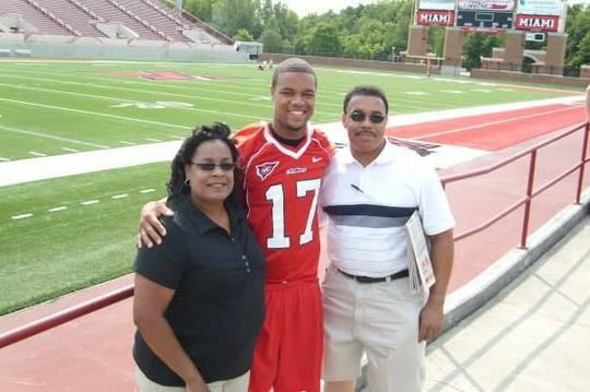 (L-R): Debra Givens, Chris Givens and Nick Givens pose on the Miami University football field where Chris played collegiately.
