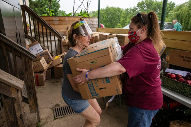 Raeann Reiber, takes a box of produce from Tina Ascough at Tikkun Farm, a 3.5 acre farm in Mt. Healthy, that will later be given away to those in need of food. They both volunteer at the farm.