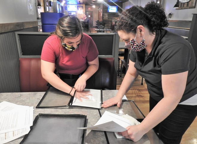 Waitress Trinity Shuman and Hostess Trhonda Blair clean menu holders and put in menu sheets at Sorrell's on the Square. The restaurant reopened for dine-in business on May 26. Employees wearing face coverings and even more thorough cleaning that before is being conducted.