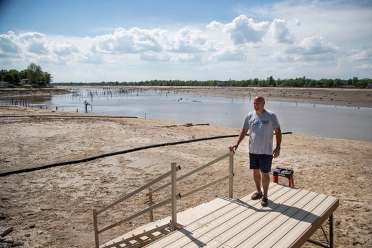 Charles Hudler of Hope Township stands by  his dock for a photo by Wixom Lake in Hope Township, Wednesday, May 27, 2020.