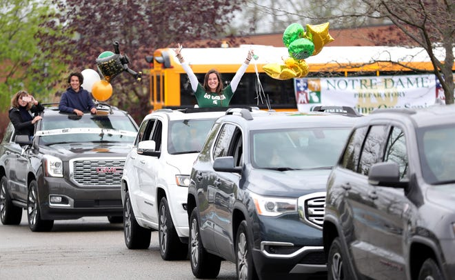 Pontiac Notre Dame Prep senior Katie Topoleski celebrates her graduation in a parade of students honking their horns as teachers waved to them and handed out tee-shirts and carnations on May 17, 2020 -- one of countless efforts by schools to recognize seniors in safe ways during the COVID crisis.