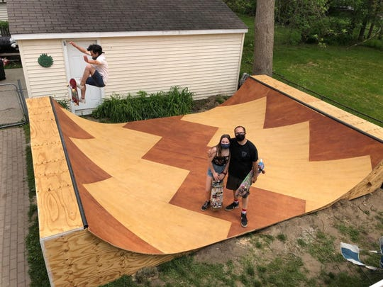 Family friend Jordan Zuppke of Royal Oak, left, tests the skate ramp, which was planned and built by Whitney Lemelin and daughter Ellie. It's 21 feet long and 4 feet tall.