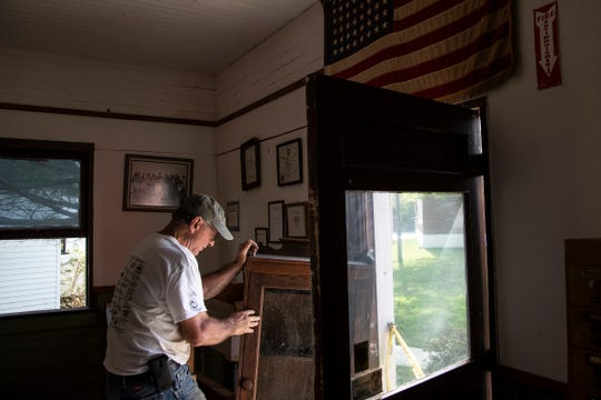 Chuck Dinsmore, president of Sanford Historic Society, checks the damage of a shelf inside of the Jerome Township Hall at the Sanford Centennial Museum in Sanford on May 27, 2020.