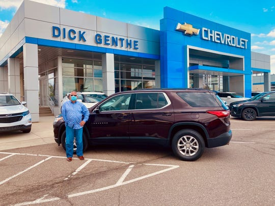 Matthew Kennedy of LaSallestands by the 2020 Chevrolet Traverse in black cherry he leased from Dick Genthe Chevrolet in Southgate.