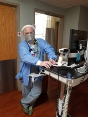 Dr. Eric Kane is wearing a face-shield and N-95 mask covered by a cloth mask over the top while on COVID-19 floor rounds at Beaumont Hospital in Trenton. Kane is a former photojournalist who left newspapers to become a doctor. He graduated from medical school in 2018.
