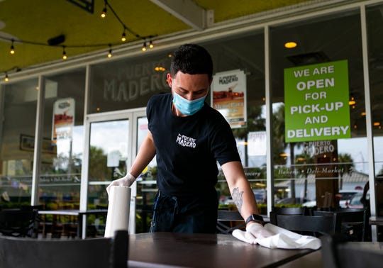 Juan Pablo Tarrago, 26, a waiter, cleans tables outside of Puerto Madero in Kendall on the first day Miami-Dade County allowed restaurants to reopen their dining rooms on Monday, May 18, 2020. In order to control the spread of the coronavirus, Miami officials prohibited restaurants from operating their dining rooms on March 16, 2020. (Matias J.