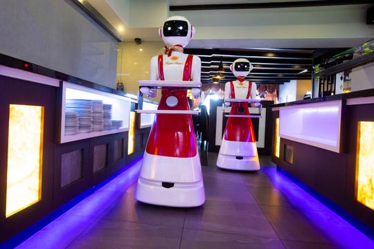 Robots advance as part of a tryout of measures to respect social distancing and help curb the spread of COVID-19 at the Hu family's Royal Palace restaurant in Renesse.
