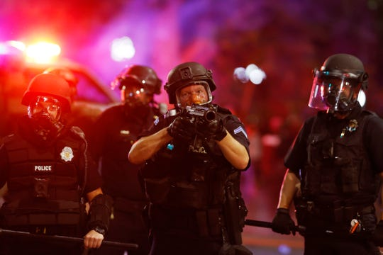 Denver police officers fire canisters to disperse a protest outside the State Capitol over the Monday death of George Floyd, a handcuffed black man in police custody in Minneapolis, Thursday, May 28, 2020, in Denver.