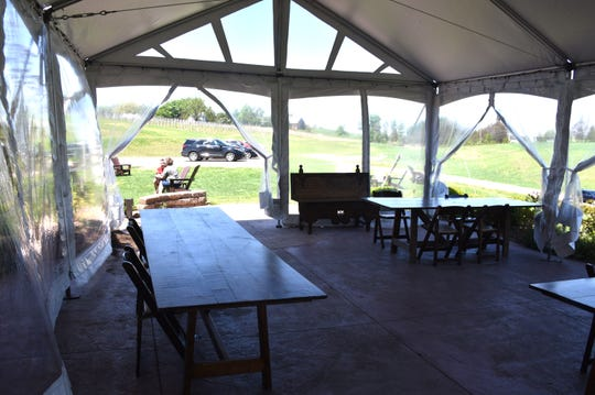 Aurora Cellars in Lake Leelanau has reevaluated service for their customers, setting up four areas for proper safety measures, including this covered seating area where only six to a table are allowed.