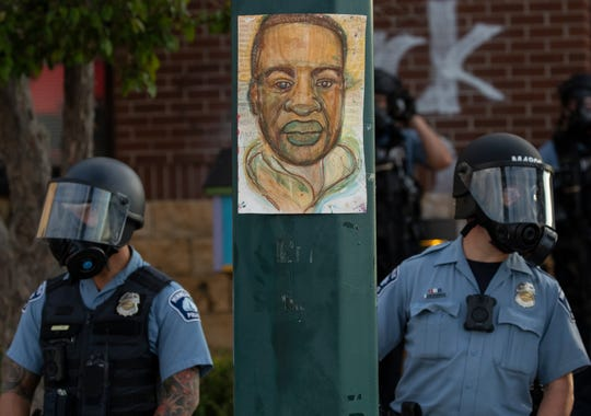 Minnesota police stand outside the department's 3rd Precinct on Wednesday, May 27, 2020, in Minneapolis. The mayor of Minneapolis called Wednesday for criminal charges against the white police officer seen on video kneeling against the neck of Floyd George, a handcuffed black man who complained that he could not breathe and died in police custody.