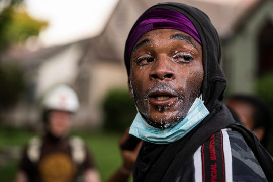 A protester used milk to mitigate tear gas as buildings near the Midway were either damaged or set on fire Thursday, May 28, 2020, in St. Paul, Minn.