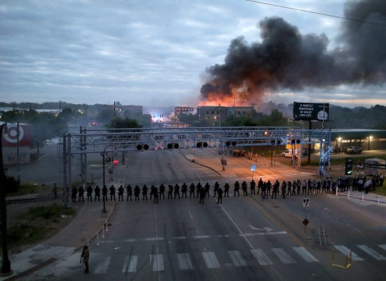 Law enforcement officers amassed along Lake Street  as fires burned after a night of unrest and protests in the death of George Floyd early Friday, May 29, 2020 in Minneapolis.   Floyd died after being restrained by Minneapolis police officers on Memorial Day.