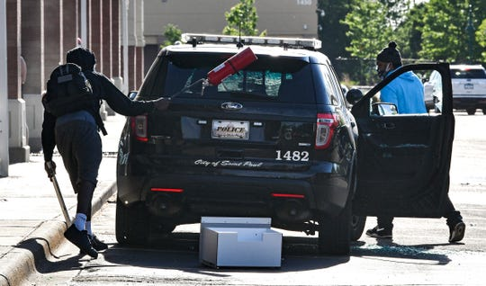 A man uses a fire extinguisher to break the rear window of a St. Paul police vehicle as another person takes items from the interior near the intersection of University Avenue West and Hamline Avenue North, Thursday, May 28, 2020, in St. Paul, Minn.