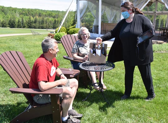 Aurora Cellars tasting room manager Dawn Bardenhagen serves an order to Mt. Pleasant residents Eric and Dana Smith on Friday, May 29, 2020. Aurora Cellars in Lake Leelanau has reevaluated service for their customers, setting up four areas for proper safety measures.