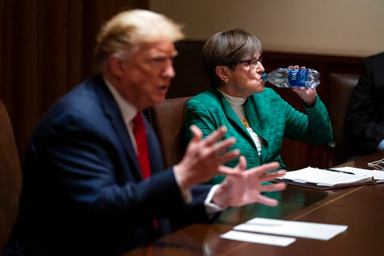Kansas Gov. Laura Kelly listens as President Donald Trump speaks during a meeting in the Cabinet Room of the White House, Wednesday, May 20, 2020, in Washington.