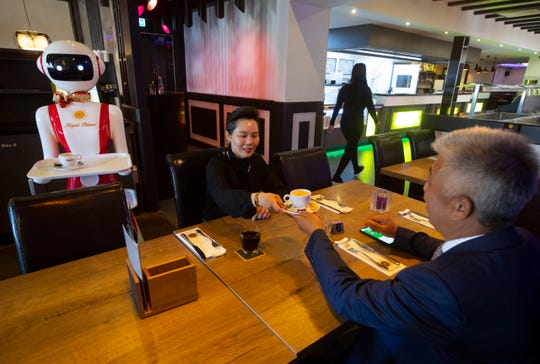 Owners Shu Lei Hu, left, and her husband Shao Song Hu, right, demonstrate the use of robots for serving purposes or for dirty dishes collection, as part of a tryout at the family's Royal Palace restaurant in Renesse.