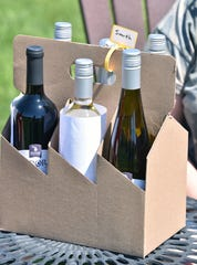 A six pack of wine-to-go is delivered to a table. Aurora Cellars in Lake Leelanau has reevaluated service for their customers, delivering orders to go at one of four outdoor sites for safe conditions for customers.