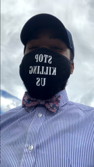 """Protest organizer Domari Greene dons a mask that says """"Stop Killing Us"""" at a protest outside the Elmira Police Department May 29, 2020 after the death of George Floyd in Minneapolis."""