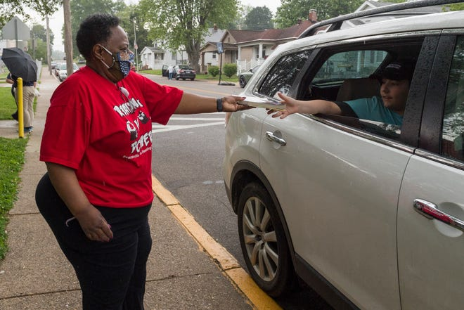 Read Evansville organizer Lana Burton, left, hands Kaden Dunbar, 11, a book after he picks up a free meal at Tekoppel Elementary School Friday afternoon, May 29, 2020. The goal Read Evansville is to distribute one thousand books a week over the summer to students in all age groups and reading levels by teaming up with multiple youth organizations throughout the community.