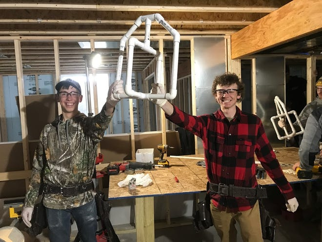 Horace Mann High School seniors  Dakota Krupp and  Wyatt Ziemer work on plumbing for a home build in North Fond du Lac. Students attend the building trades cooperative hosted by the North Fond du Lac School District.