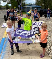 Children hold up a sign to recognized graduating seniors of Suring High School, who drove through the community in special parade on May 23.