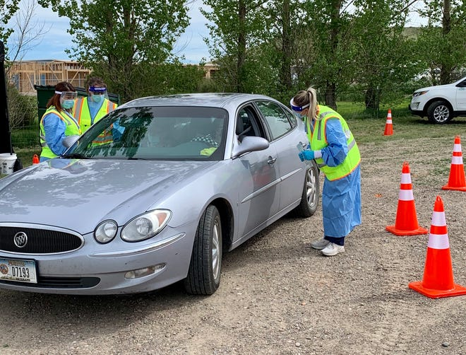 Alluvion Health workers assist two women who stopped by the Little Shell Tribe's COVID-19 drive-thru testing site.