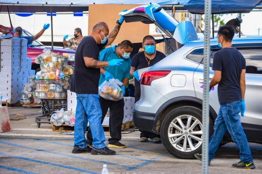Employees from the Department of Public Works' Busing Operations and Building Maintenance divisions, and others, coordinate their efforts in placing Disaster Household Distribution food commodity bags into the vehicles of patrons during a food distribution at the Farmers' Market in Dededo on Friday, May 29, 2020.