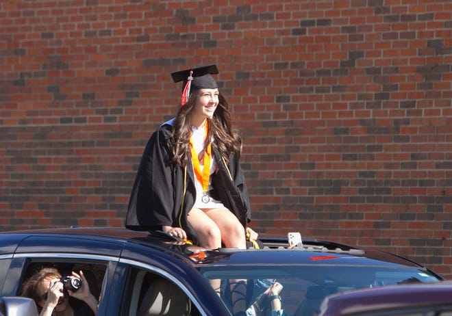 Alexis Moskowitz and many fellow 2020 Brighton High School graduating seniors prop up in moon roofs of the cars they ride in the parade around the high school Friday, May 29, 2020.