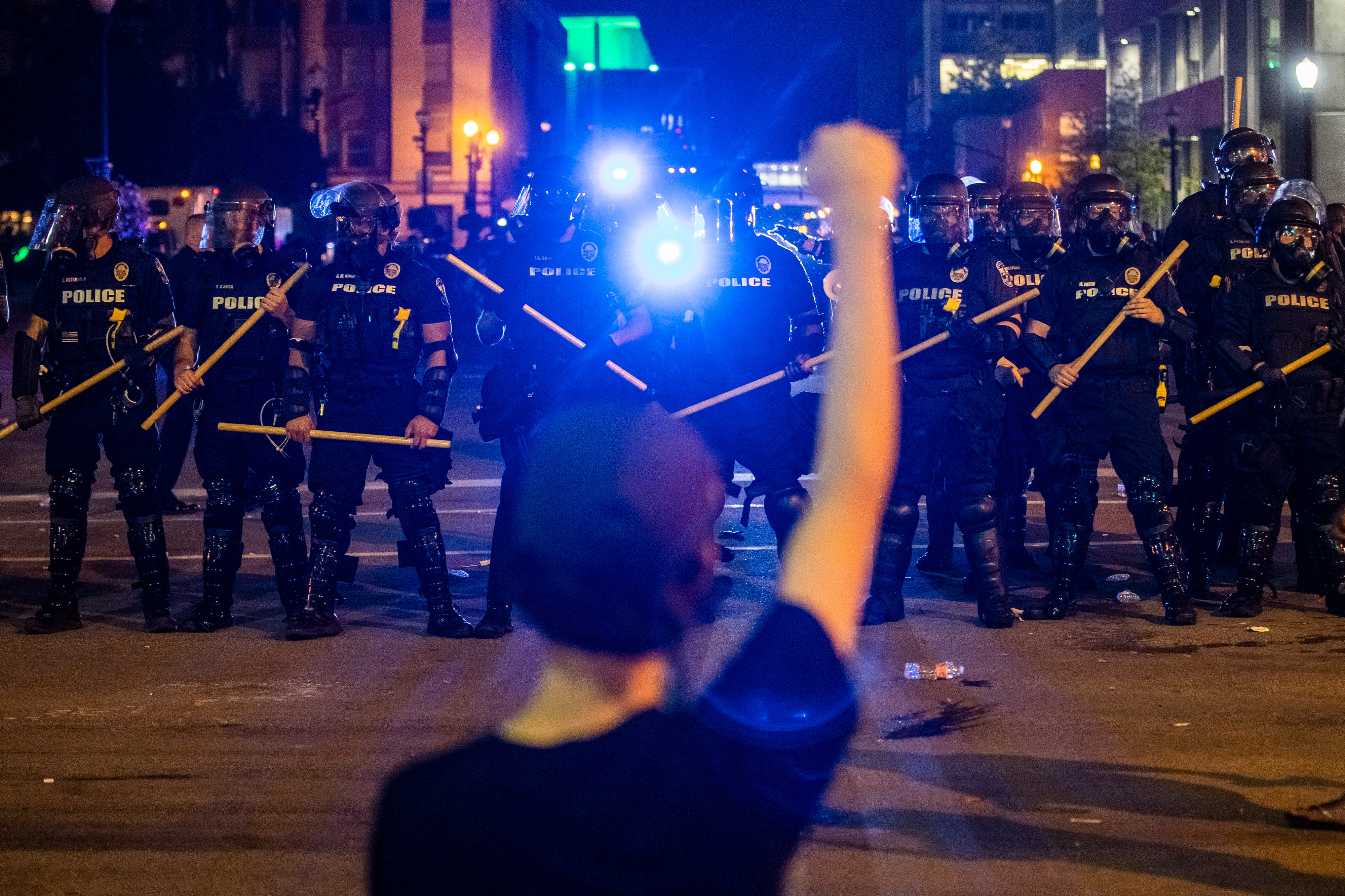 A protester raises a fist into the air early Friday morning as the deaths of Louisville's Breonna Taylor and Minneapolis' George Floyd at the hands of police spurred protests. May 29, 2020