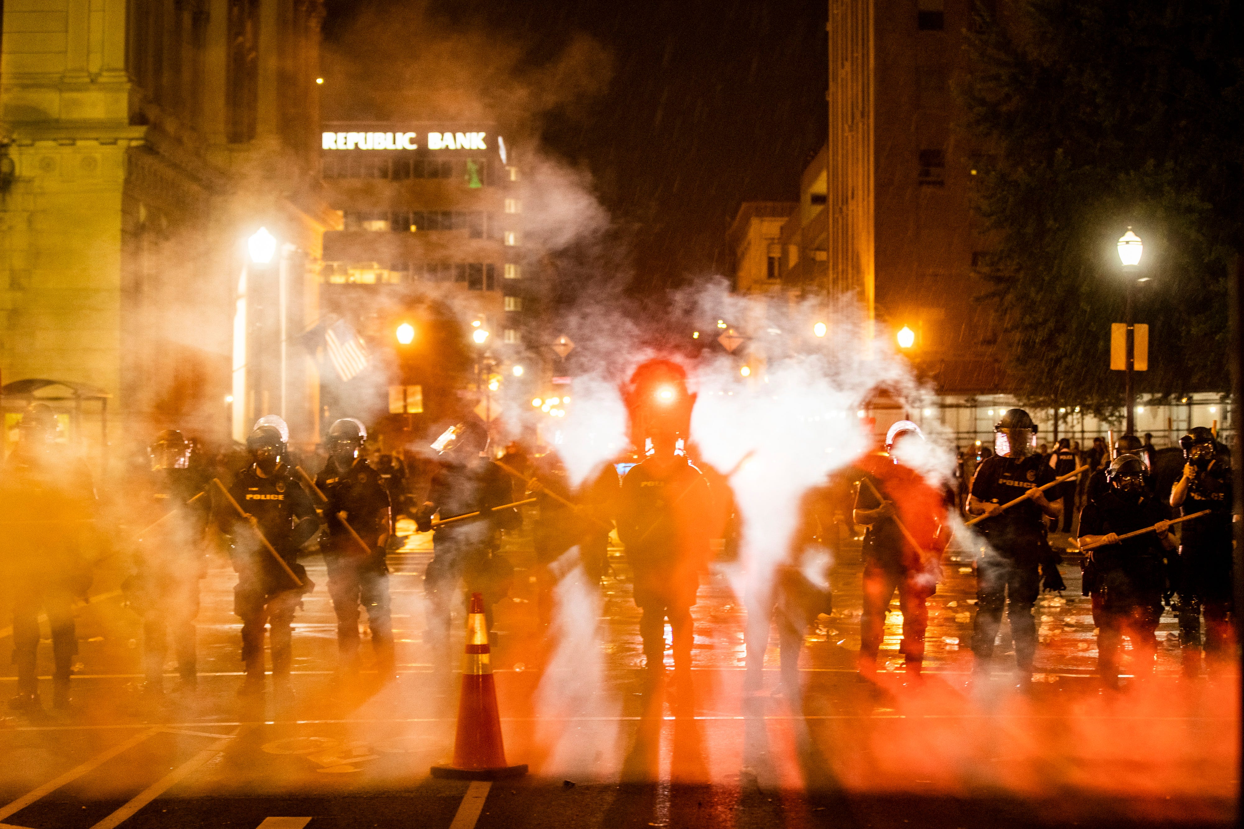 Louisville police move through a cloud of tear gas early Friday morning as the deaths of Louisville's Breonna Taylor and Minneapolis' George Floyd at the hands of police spurred protests. May 29, 2020