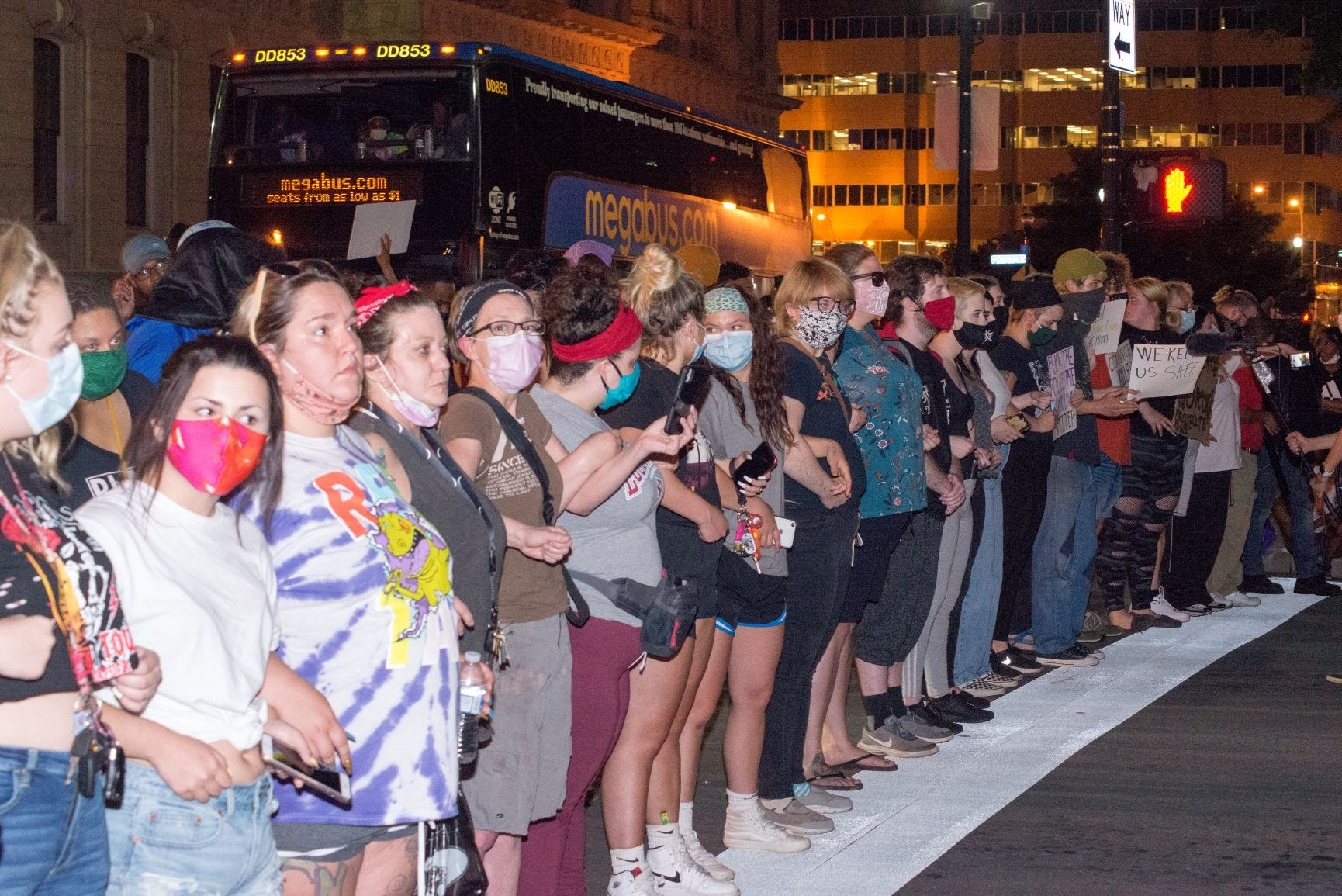 A line of almost all white women formed between police officers and black protesters at a rally in downtown Louisville calling for justice in the death of Breonna Taylor.