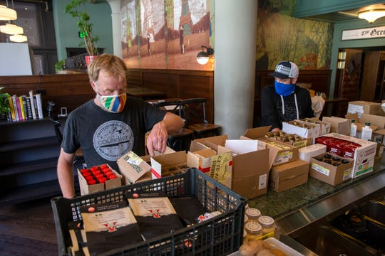 Fauntleroy owners Dan Van Rite, left, and Dan Jacobs work to set up grocery displays at the restaurant. In June, Fauntleroy, which had been closed to indoor dining for several months, opened a market at the front of the restaurant selling local goods and produce.