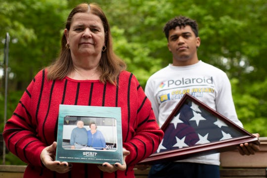 Florence Hopp, left, holds a photograph of herself and her husband Robert Hopp during a cruise in 2017, as her son J.J. Brania-Hopp holds the American flag the military presented to them after his father's death. Hopp was one of at least 79 residents of a veterans home in Paramus, New Jersey, to die from COVID-19, making the state-run facility one of the nation's worst hot spots for the virus. (AP Photo/Mary Altaffer, Friday, May 22, 2020)