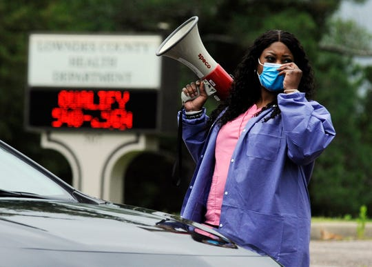 """In this May 27, 2020, photo, healthcare worker Tonya Wilkes adjusts her mask while working at a Lowndes County coronavirus testing site in Hayneville, Ala. Experts say Lowndes County and nearby poor, mostly black counties in rural Alabama are now facing a """"perfect storm"""" as infections tick up."""