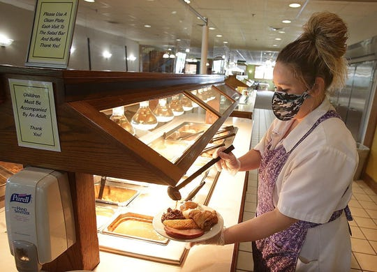 Cindy Fulton, a server at the Amish Door Restaurant in Wilmot, puts together a diner's plate at their newly designed buffet. A server will now get the items for guests.