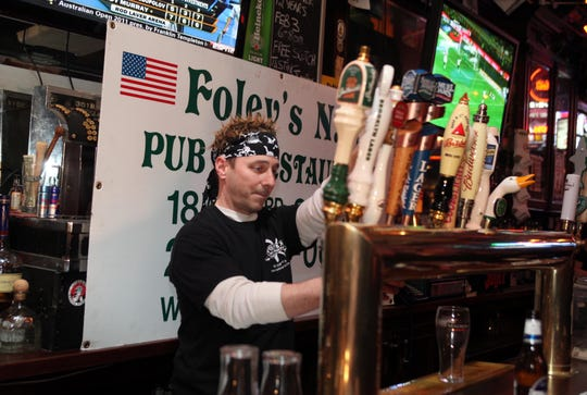 Yankees general manager Brian Cashman wears a wig and bandana in 2011 as he serves as guest bartender at Foley's Pub in Manhattan for Ed Randall's Bat for a Cur - a charity which promotes prostate cancer awareness.