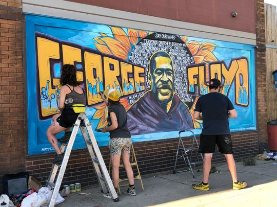 A group of artists honor George Floyd by painting a mural on the wall of the Cup Foods at the corner of 38th Street and Chicago Avenue south in Minneapolis on Thursday, May 28, 2020. Artists began work on the mural that morning.