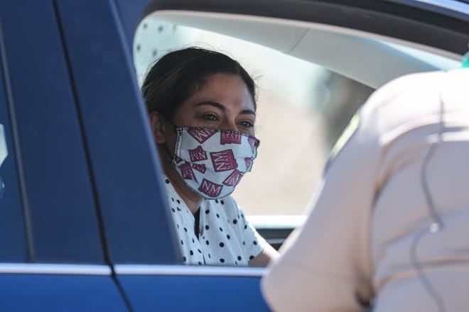 The Doña Ana Sheriff's Office distributes cloth face coverings to residents curbside of the Doña Ana County Government Center in Las Cruces as a line of cars stretches out the parking lot and down the street on Friday, May 29, 2020.