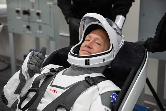 NASA astronaut Douglas Hurley rehearses putting on his SpaceX spacesuit in the Astronaut Crew Quarters inside the Neil A. Armstrong Operations and Checkout Building at the agency's Kennedy Space Center in Florida on May 23, 2020, during a full dress rehearsal ahead of NASA's SpaceX Demo-2 mission to the International Space Station.