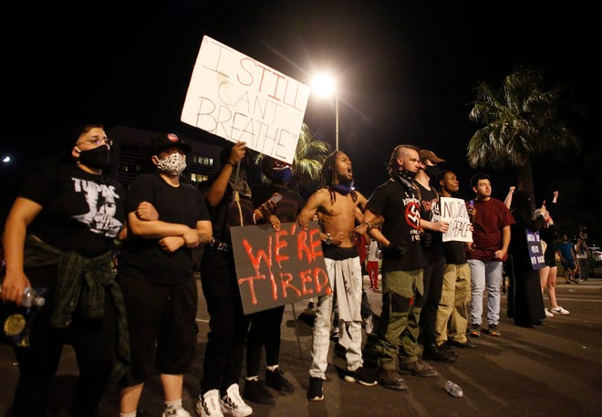 Protesters line up and stare down police officers near 7th ave and Washington during a Justice for George Floyd rally in downtown Phoenix, Ariz. on May 28, 2020.