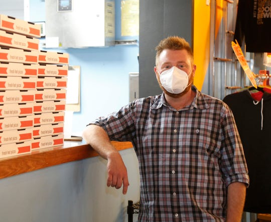 Sloop Brewing co-founder Adam Watson beside a stack of to go pizza boxes at Sloop Brewing in Hopewell Junction on May 21, 2020. WIth restrictions due to COVID-19 the brewery and restaurant has had to focus on online sales and to go orders.