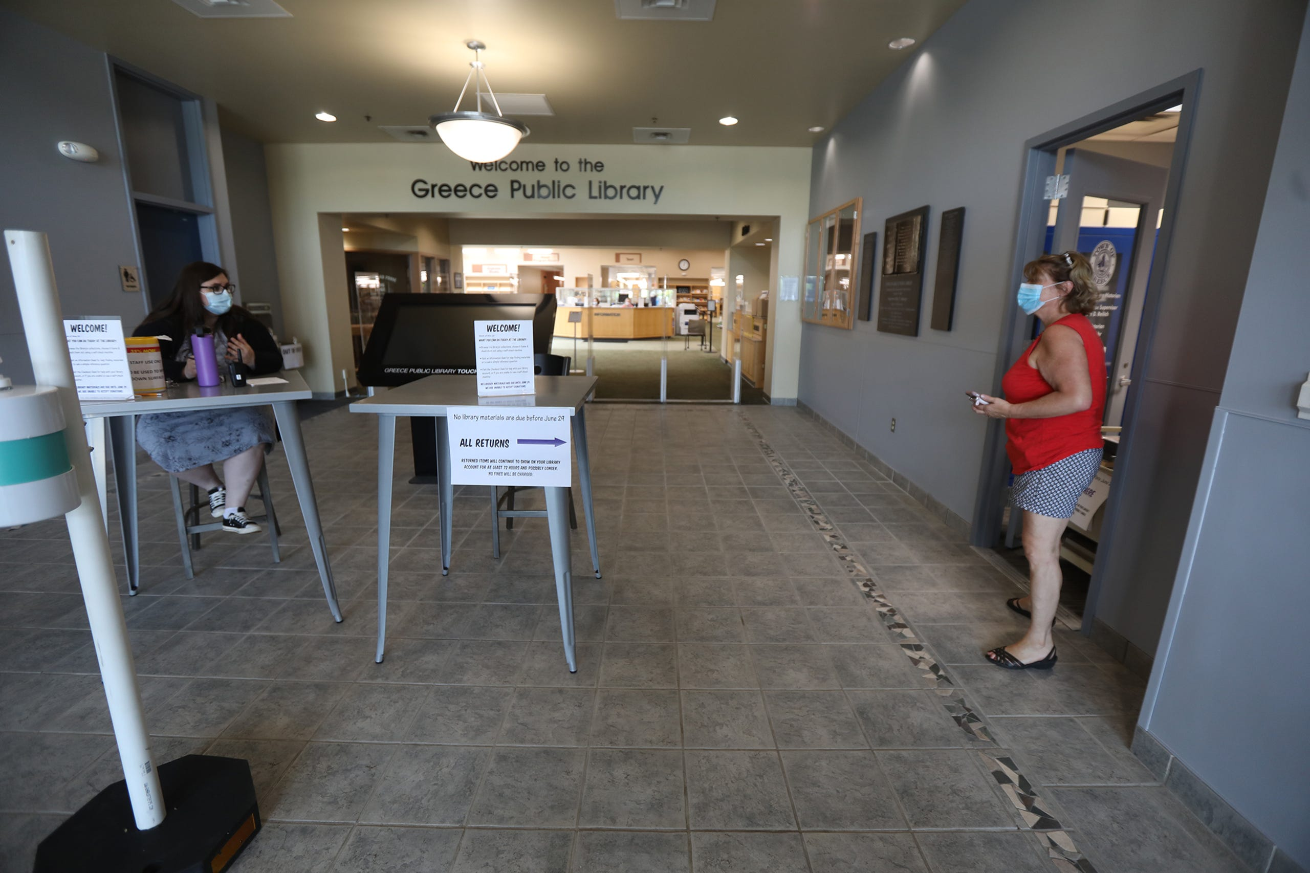 The Greece Public Library opened earlier this week with limited services and days and hours of operation.  A few people were seen browsing books and audio books to check out, Friday, May 29, 2020.  Librarian Stephanie Cervantes answers a question from Marie Kraft who was returning a book.