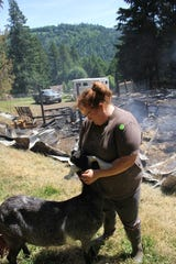 Morgan Yeats and her goat, Roni, stand in front of the smoldering barn on her farm south of Silverton.