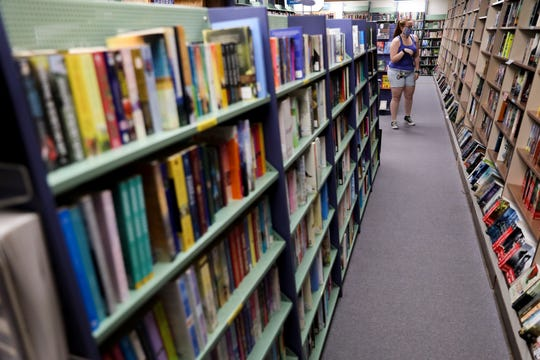 Brittany Harlow looks at fantasy and the science fiction section at The Book Bin in Salem, Oregon, on May 29, 2020. Customers are only allowed in one at a time, by appointment to browse and are encouraged to maintain social distancing guidelines with employees.