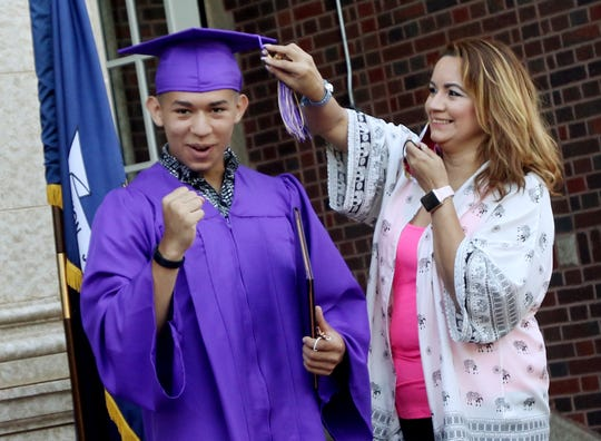 Byrd's Columbus Espree reacts as his mother, Lucy Espree, moves his tassel to indicate his graduation in a small private ceremony in which Bryd Principle Jerry Badgley handed Espree the diploma. Four ceremonies, in front of the school, are for students who are departing early for the military and will not be able to make the rescheduled graduation on Aug. 1st.